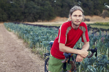Smiling man with bicycle standing by crops on field