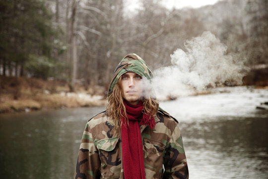 Man in hooded camouflage jacket standing by lake on cold winter day