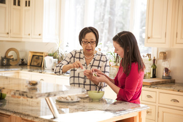 Mother and daughter making dumplings in kitchen