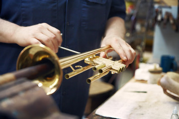 Midsection of man making trumpet in workshop