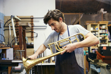 Man shaping trumpet while working in workshop