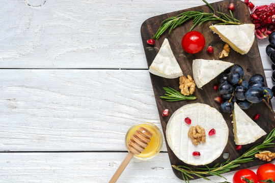 camembert cheese with grapes, tomatoes cherry, pomegranate seeds, walnuts and rosemary on wooden cutting board