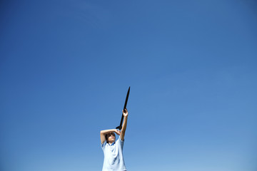 Low angle view of boy holding rocket against clear blue sky