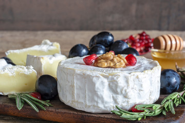 delicious camembert cheese with grapes, pomegranate seeds, honey walnuts and rosemary on wooden cutting board