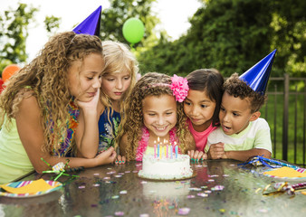 Happy curious children looking at birthday cake on table in backyard