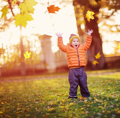 Child standing with umbrella in beautiful autumnal day