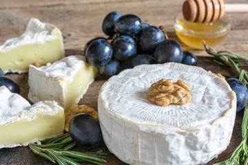 camembert cheese with grapes, honey walnuts and rosemary on wooden cutting board