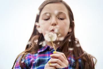Girl blowing dandelion against sky