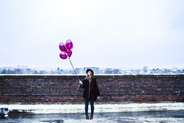 Woman holding pink balloons on winter day