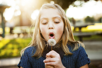 Girl blowing dandelion in park