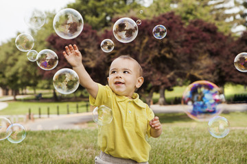 Boy playing with soap bubbles in park