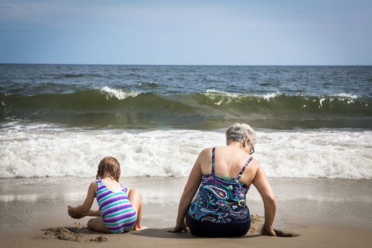 Rear view of grandmother with granddaughter digging sand while sitting at beach