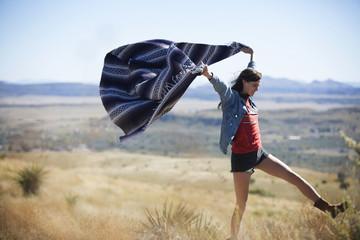 Happy woman waving blanket on field against clear sky
