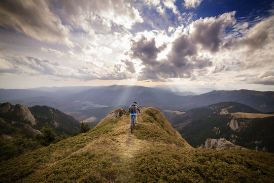 Backpacker riding bicycle on mountain