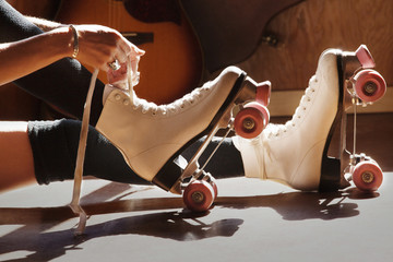 Low section of woman tying roller skates at home