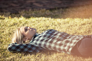 Side view of thoughtful woman lying on grassy field