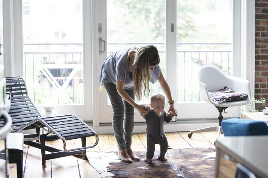 Mother helping baby to walk in living room