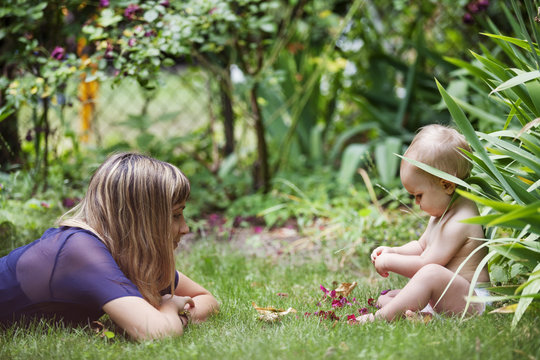 Mother looking at daughter playing with flower at backyard