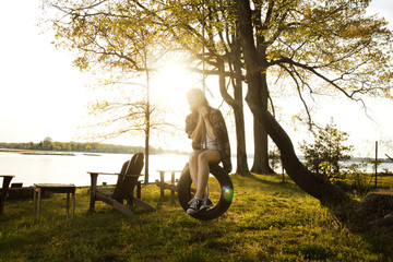 Thoughtful woman sitting on tire swing against sky