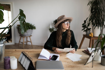 Young freelancer wearing hipster hat and glasses working project in modern office. Skilled worker planning strategy. Brainstorming. Beautiful woman studying at university library. Exam preparation.