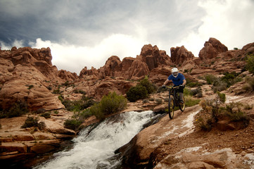 Cyclist riding on rocks by river against cloudy sky