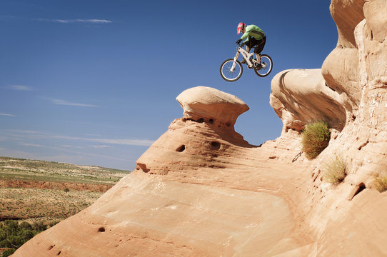 Male cyclist jumping from mountain against blue sky