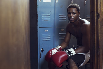 Portrait of boxer sitting in locker room