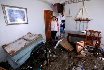 Lisa Varona walks through her business' building damaged by Hurricane Michael in Mexico Beach