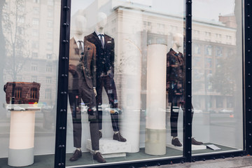 Manikins dressed in autumn male outfits on showcase of a store in city center. Shopping and sales concept