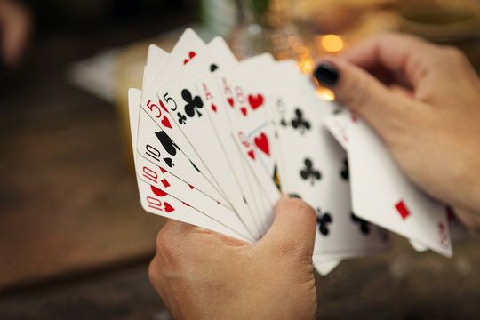 Close up of woman's hands holding playing cards