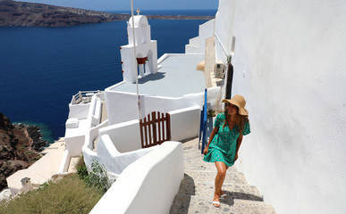 Young fashion woman with green dress and hat walking on stairs in Oia, Santorini. Female travel tourist on her summer vacations in Greece.