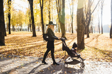 A young stylish mother carries her little son in a wheelchair in the autumn Park.