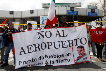 "Members of civil organisations hold a sign reading ""No to the airport"" as they occupy toll booths, allowing the free access to motorway in protest against the construction of the new Mexico City international airport in Texcoco"