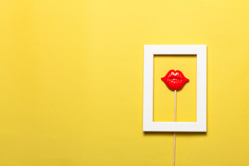 Frame with red lips inside on yellow background.
