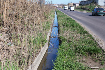 Dirty sewage and household rubbish in small river, irrigation channel causes rapid growth of algae. Water pollution. Ecological problem. Problem of plastic. Use of water is dangerous, it is forbidden