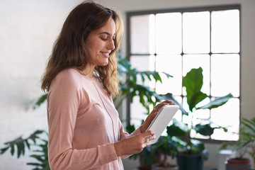 Woman smiling while using her digital device at home