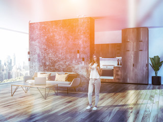 Woman with smartphone in living room interior
