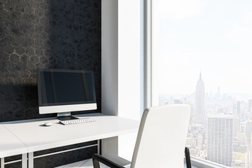 Office workplace with computer, black wall