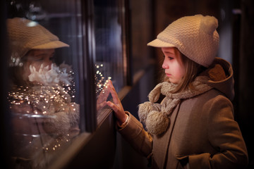 Young girl looking on windows shopping, with illuminated christmas garland.