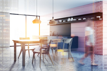 Woman in pink tile kitchen interior, table