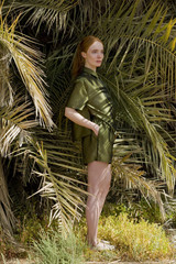 young woman with red hair in green clothes behind palm leaves