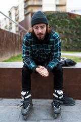Hipster young man wearing roller skates sitting on bench in the street.