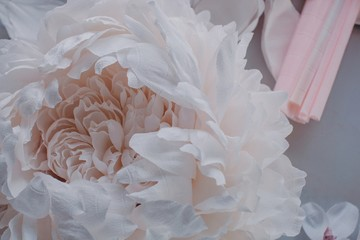 From above crop big delicate paper peony on the table