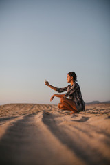 Content young woman taking photo with cell phone on the beach at