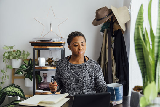 Woman At Home with Notebook