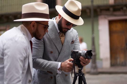 Two stylish men setting up a video camera