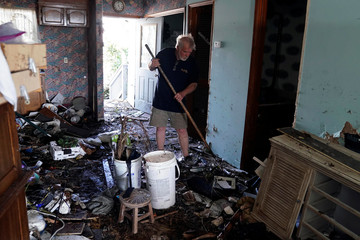 A man cleans out his kitchen with a rake after he rode out the hurricane in his home following Hurricane Michael in Mexico Beach