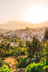 orange light over Chefchaouen, Morocco and Rif mountains panoramic view during sunset golden hour. Chefchaouen is a city in northwest Morocco. Chefchaouen is noted for its buildings in shades of blue.