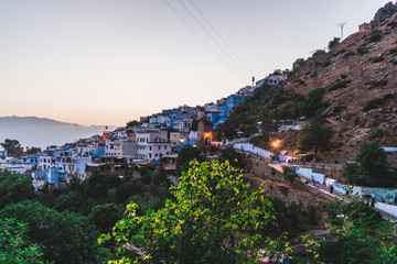 Chefchaouen blue city evening view from the hill with blue houses and street lamps light in Morocco