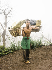Smoking laborer with baskets of sulfur